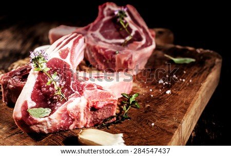 Close Up of Raw Lamb Filets Seasoned with Garlic, Salt and Fresh Herbs on Rustic Wooden Board - stock photo