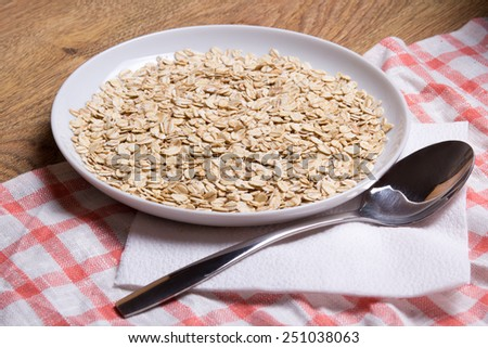 close up of raw oatmeal in plate with spoon on table - stock photo