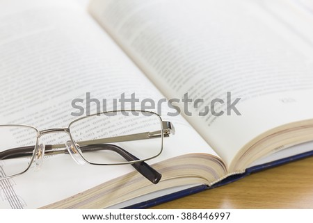 Close up of reading glasses and a book on the desk - stock photo