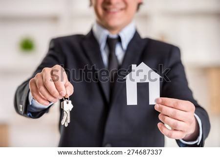 Close-up of realtor man is showing a model of home and keys. - stock photo