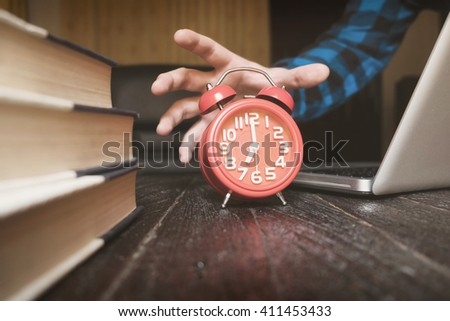 Close up of red alarm clock on work desk with text book, laptop and hand try to stop a noise - stock photo