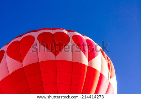 Close up of red and pink heart hot air balloon with bright blue sky taking off at balloon festival - stock photo