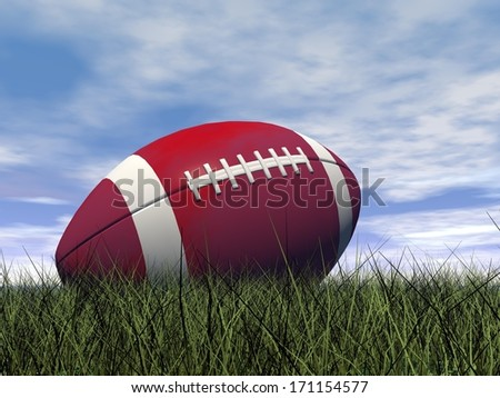 Close up of red and white rugby ball on green grass by beautiful day - stock photo