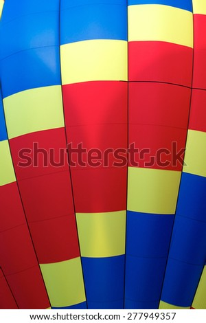 Close up of red, blue, and yellow hot air balloon showing the gentle curve of the air ship. - stock photo