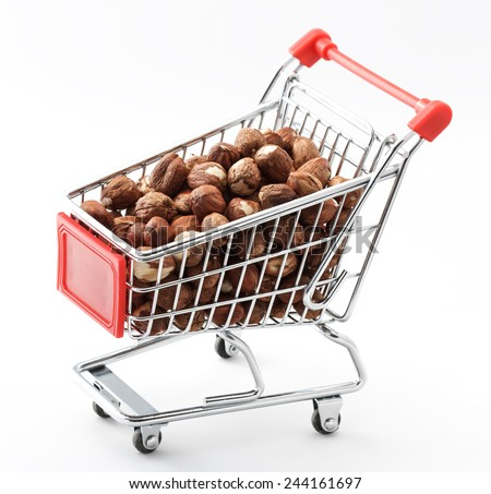 close up of red chrome shopping cart with hazelnuts on white background - stock photo