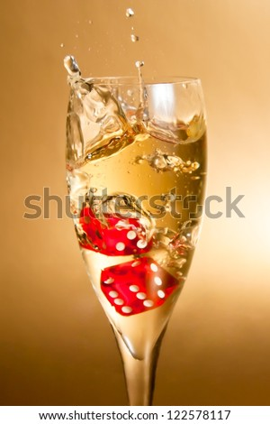 close-up of red dice in a flute with gold bubbles on golden background - stock photo