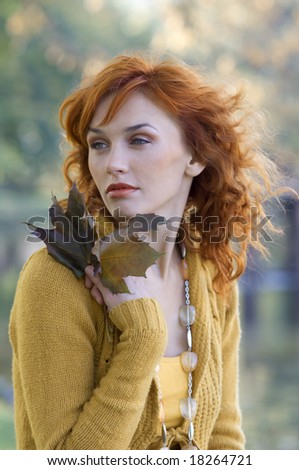 close up of red-haired woman with some leaves near face in park - stock photo
