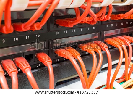 Close up of red internet ethernet network cables connected to black switch in data center - stock photo