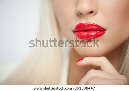Close up of red lips of attractive blond girl. She is touching her chin with arm gently. The lady is expressing confidence - stock photo