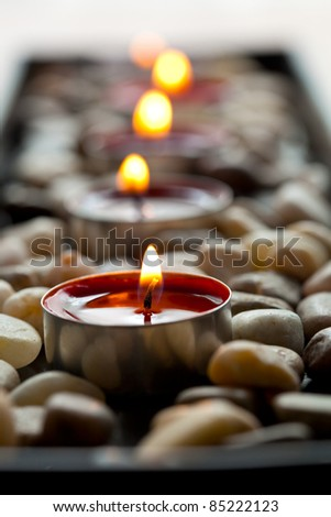Close-up of red tea-light candles on pebbles - stock photo