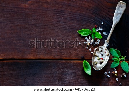 Close up of red, white and black pepper with pink salt spice in spoon and herbs over old wood. Classic mixed spices for cooking. Top view with copy space - stock photo