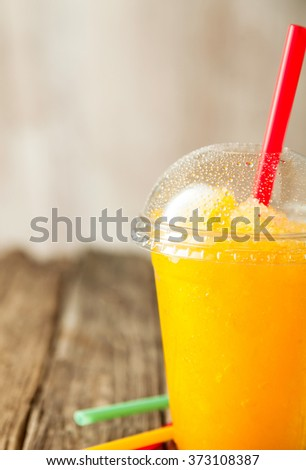 Close Up of Refreshing and Cool Bright Orange Slush Drink in Plastic Cup with Lid Served on Rustic Wooden Table with Collection of Colorful Drinking Straws - stock photo