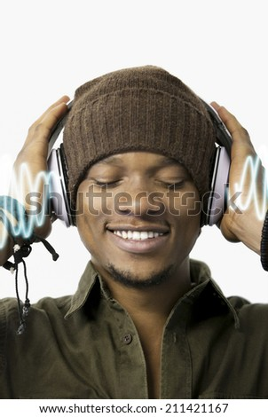 Close-up of relaxed young man listening music through headphones - stock photo