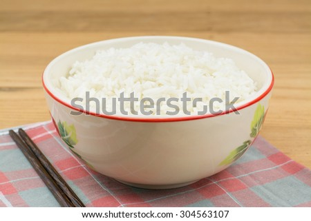 close up of rice in wooden in bowl on wooden table - stock photo