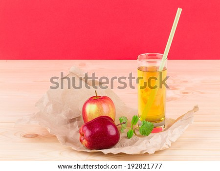 Close up of ripe red apples and glass of juice. - stock photo