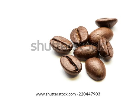 Close-up of roasted coffee beans heap isolated on white. Studio shot. - stock photo