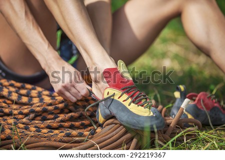 Close up of rock climber putting on climbing shoes while sitting on grass - stock photo
