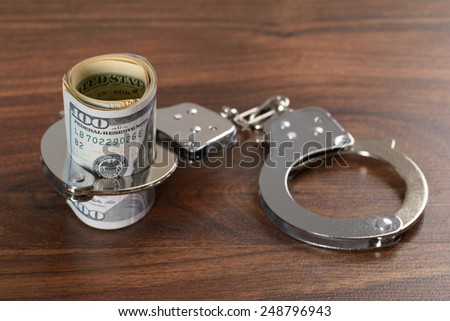 Close-up Of Rolled Up Dollar Bills With Handcuffs - stock photo