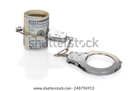 Close-up Of Rolled Up Dollar Bills With Handcuffs On White Background - stock photo