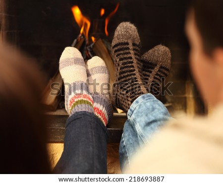 Close up of romantic legs of a couple in socks in front of fireplace at winter season at home - stock photo