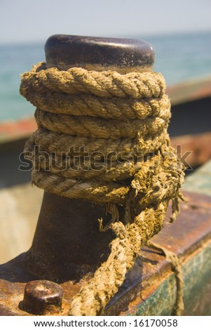 Close-up of rope wrapped around rusty fishing boat cleat - stock photo