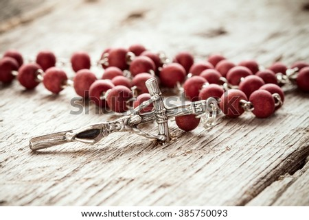 Close-up of  rosary on old wooden texture background - stock photo