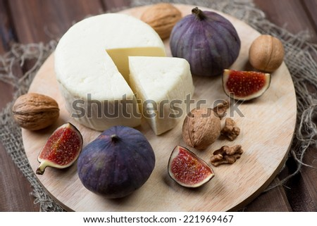 Close-up of round cheese, whole and sliced figs, walnuts - stock photo