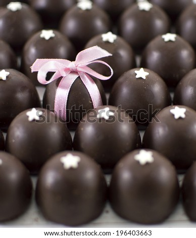 Close up of round chocolate candies and one candy with pink bow - stock photo