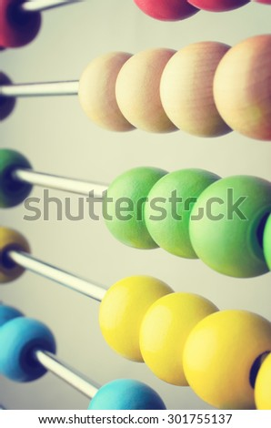 Close up of rows of abacus beads in bright colours,  angled and leading away into soft focus. Cross processed to create retro effect. - stock photo