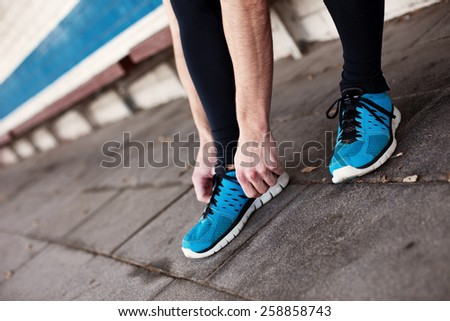 close up of runners's legs, tie shoelaces - stock photo