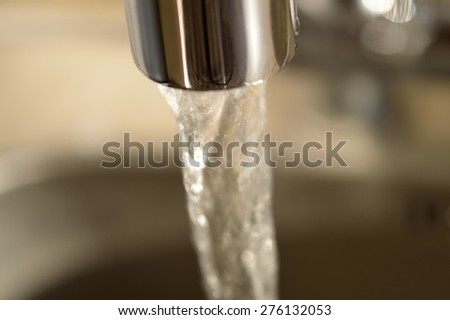 Close-up of running water from a faucet. - stock photo