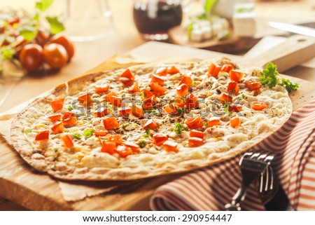 Close Up of Rustic Thin Crust Pizza on Wooden Cutting Board Surrounded by Fresh Ingredients and Cutlery - stock photo