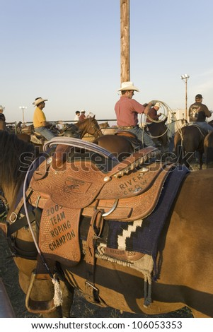 Close-up of saddle and cowboy at PRCA Rodeo at Lower Brule, Lyman County, Lower Brule Sioux Tribal Reservation, South Dakota, 58 miles Southeast of Pierre near Missouri River, August 10, 2007 - stock photo