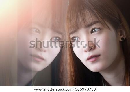 Close up of sadness girl is sad at the window with reflection of her face. - stock photo