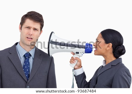 Close up of saleswoman with megaphone yelling at colleague against a white background - stock photo
