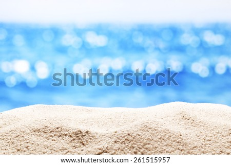 Close up of  sand with blurred sea background. - stock photo
