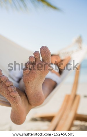 Close up of sandy feet of woman sleeping in a hammock on the beach - stock photo