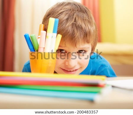 Close-up of schoolboy looking at camera with smile - stock photo