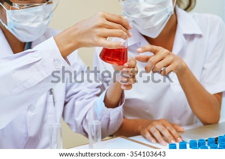 close up of scientists examining with chemicals in laboratory  - stock photo
