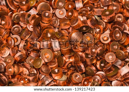 Close up of scrapheap of copper from hole punching process, waiting for recycling - stock photo