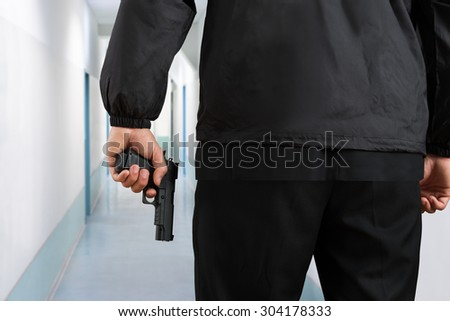 Close-up Of Security Guard Holding Black Pistol In Hands - stock photo