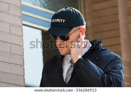 Close-up Of Security Guard Standing In Front Of The Entrance Listening To Earpiece - stock photo