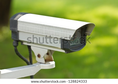 Close up of security surveillance camera isolated on green background. - stock photo