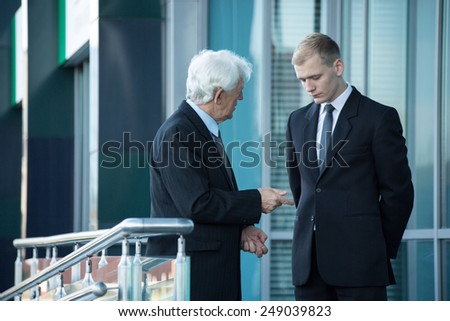 Close-up of senior businessman talking with his employee - stock photo