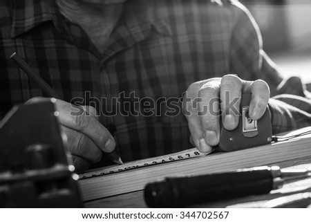 Close up of senior carpenter hands marking a measurement on a wooden plank, black and white. - stock photo