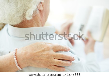 Close-up of senior female hand on her husband shoulder during reading - stock photo