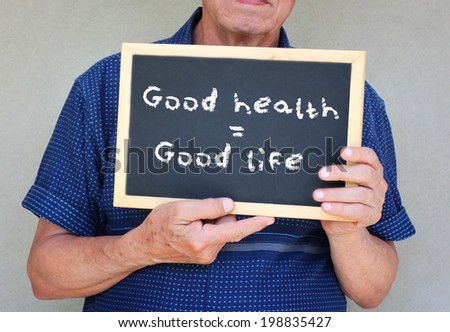 close up of senior man holding a blackboard with the phrase good health equals good life - stock photo