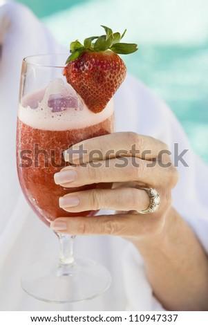 Close-up of senior woman's hand holding glass of strawberry shake - stock photo