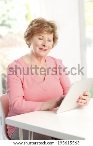 Close-up of senior woman using digital tablet and surfing on internet - stock photo