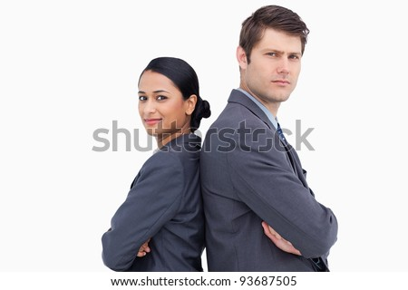 Close up of serious salesteam standing back to back against a white background - stock photo